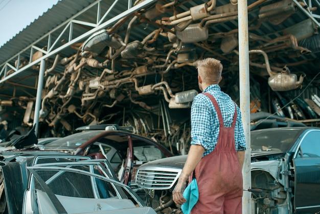 Meccanico maschio alla pila di auto sulla discarica. rottami di automobili, cianfrusaglie di veicoli, rifiuti di automobili. trasporto danneggiato e schiacciato, cantiere di demolizione