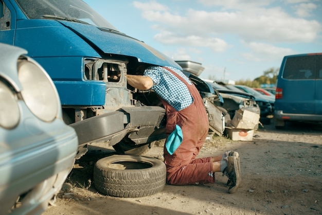 Un meccanico maschio ha infilato la testa sotto il cofano in una discarica di auto. rottami di automobili, cianfrusaglie di veicoli, rifiuti di automobili. trasporti abbandonati, danneggiati e frantumati, cantiere di demolizione