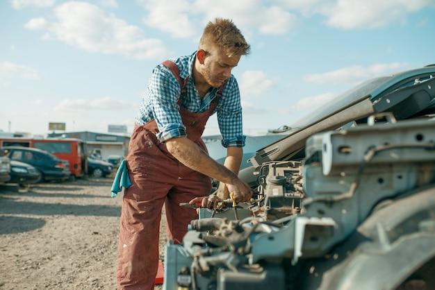Il meccanico maschio svita il motore sulla discarica di auto. rottami di automobili, cianfrusaglie di veicoli, rifiuti di automobili. trasporti abbandonati, danneggiati e frantumati, cantiere di demolizione