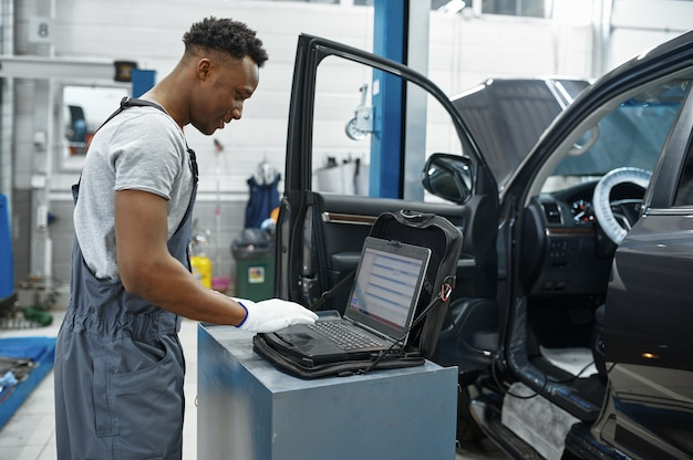 Meccanico maschio che utilizza laptop all'auto con cofano aperto, servizio auto