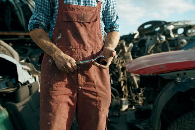 Meccanico maschio in vetri di saldatura su discarica di auto. rottami di automobili, cianfrusaglie di veicoli, rifiuti di automobili. trasporto abbandonato e frantumato, scrapyard