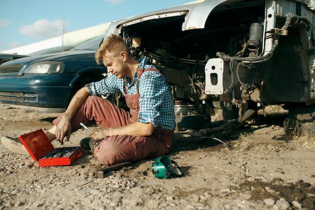 Meccanico maschio in vetri di saldatura su discarica di auto. rottami di automobili, cianfrusaglie di veicoli, rifiuti di automobili. trasporti abbandonati, danneggiati e frantumati, cantiere di demolizione