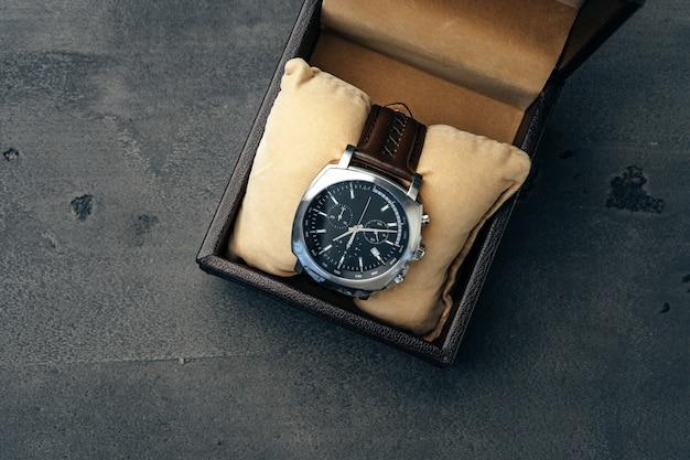 Orologio meccanico maschio sulla superficie di cemento scuro si chiuda