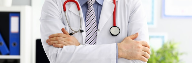 Mani di medico di medicina maschile incrociate sul petto