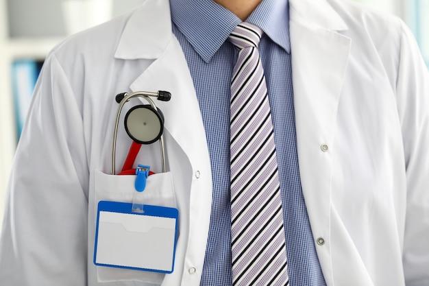 Petto di medico terapeuta di medicina maschio con lo stetoscopio in primo piano tasca. strumenti medici e strumenti negozio fisico e prevenzione delle malattie esame paziente 911 concetto di stile di vita sano