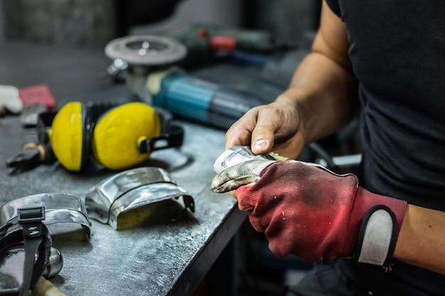 Operaio metallurgico maschio assemblaggio pezzo di armatura medievale. man mano il trattamento di parti metalliche di hardware in un'officina
