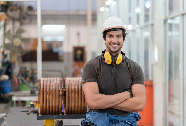 Operaio metallurgico maschio in casco protettivo che sorride e che sta rilassato