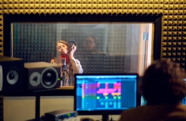 Musicista maschio e cantante femminile, interni di studio di registrazione sullo sfondo. sintetizzatore e mixer audio, posto di lavoro del musicista, processo creativo