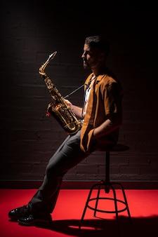 Musicista maschio sotto i riflettori tenendo il sassofono