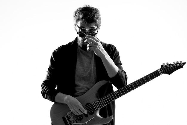 Musicista maschio con rock star di musica per chitarra su sfondo chiaro.