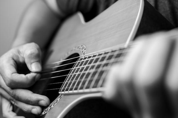 Musicisti maschi che suonano la chitarra acustica. i musicisti del primo piano stanno suonando la chitarra acustica. i musicisti maschi tengono gli accordi e la chitarra strimpellata.