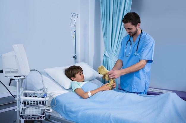 Infermiere maschio che dà orsacchiotto al paziente durante la visita in reparto