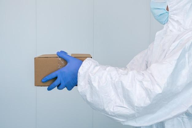Un infermiere in tuta protettiva ppe mostra una scatola in ospedale. l'operatore sanitario riceve forniture mediche per curare i pazienti con coronavirus o covid 19. medico che indossa un dpi.
