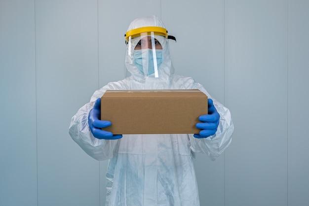 Un infermiere in tuta equipaggiamento protettivo e schermo facciale mostra una scatola in un ospedale. l'operatore sanitario riceve forniture mediche per prendersi cura dei pazienti con coronavirus o covid 19.