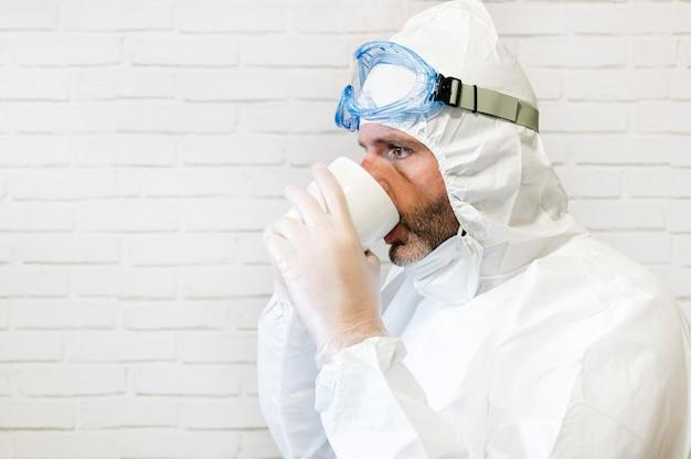 Infermiera maschio che indossa tuta protettiva e abiti da lavoro bevendo una tazza di caffè durante la pausa