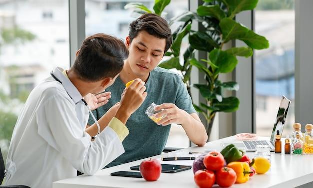 Nutrizionista maschio che mostra e discute pillole di vitamine con un uomo asiatico mentre è seduto a tavola con cibo sano mentre lavora in un ospedale moderno