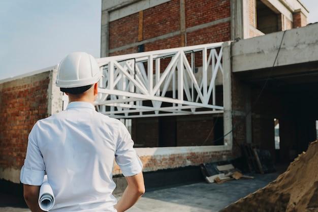 Proprietario maschio che osserva come sta andando il lavoro sull'edificio in costruzione all'esterno dell'edificio.
