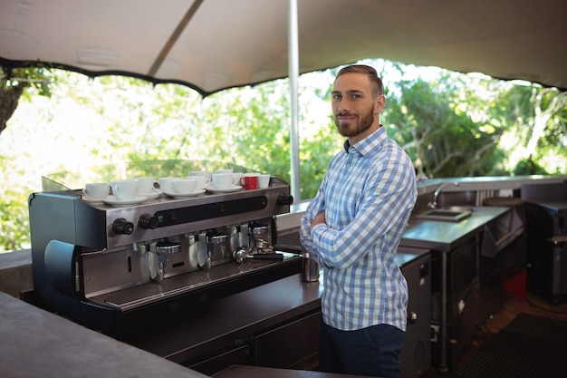 Proprietario maschio in piedi con le braccia incrociate al caffè all'aperto