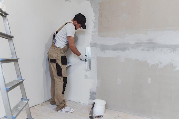 Pittore maschio con una spatola in mano fa le riparazioni in th