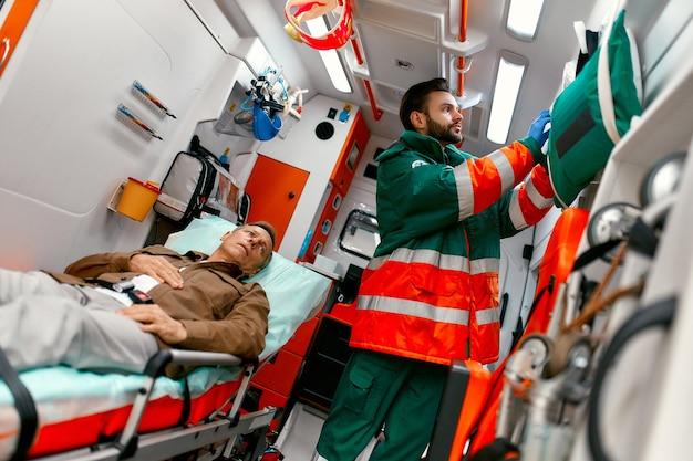 Un paramedico in uniforme cerca una maschera per l'ossigeno per aiutare un paziente anziano sdraiato su una barella in una moderna ambulanza.