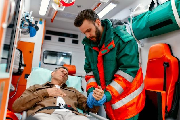 Un paramedico maschio in uniforme misura il polso di un paziente anziano disteso su una barella in una moderna ambulanza.