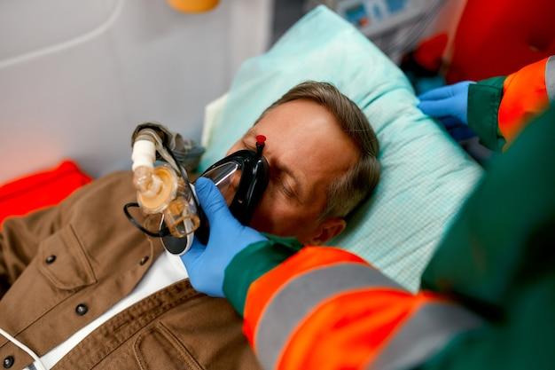 Un paramedico maschio in uniforme mette su un ventilatore con ossigeno per aiutare un paziente anziano sdraiato su una barella con un pulsossimetro in una moderna ambulanza.