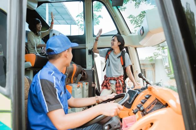 Un passeggero maschio è salito sull'autobus con una mano salutando quando ha incontrato il suo gruppo di amici a bordo dell'autobus