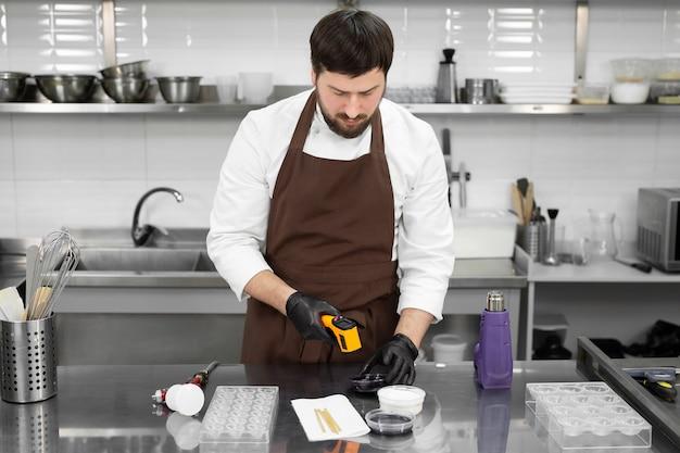 Il pasticcere maschio misura la temperatura della glassa al cioccolato con un termometro senza contatto