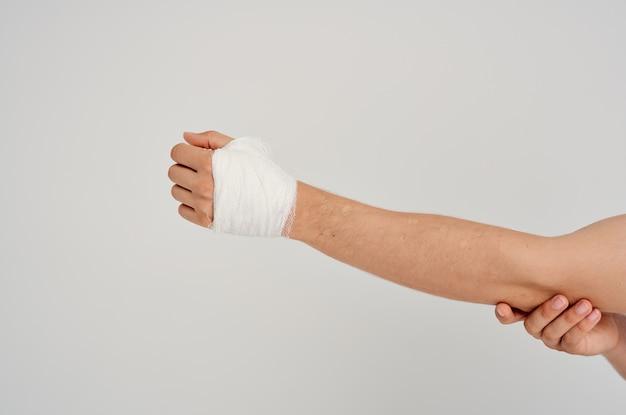 Paziente maschio bendato lesione alla mano alle dita ricovero in ospedale sfondo chiaro. foto di alta qualità