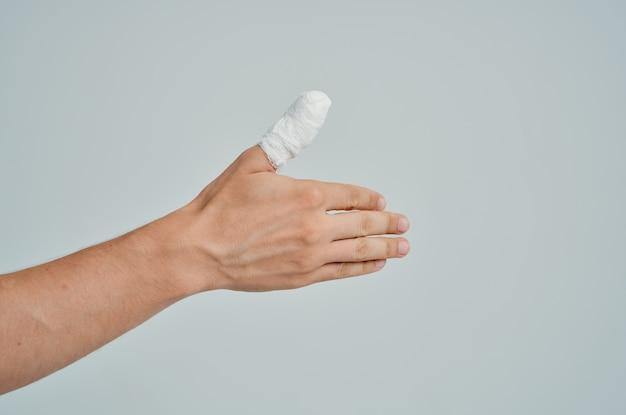 Problemi di salute del trattamento delle lesioni alla mano del paziente maschio sfondo chiaro. foto di alta qualità