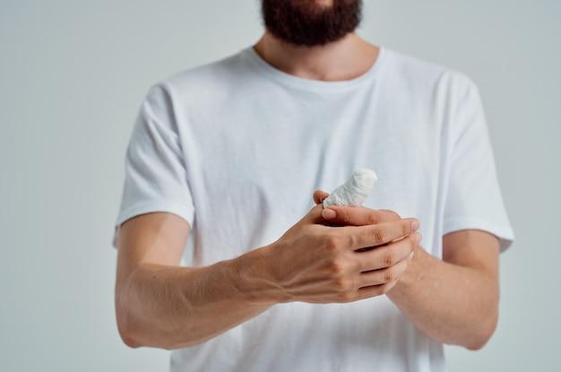 Problemi di salute del trattamento delle lesioni alla mano del paziente maschio sfondo chiaro