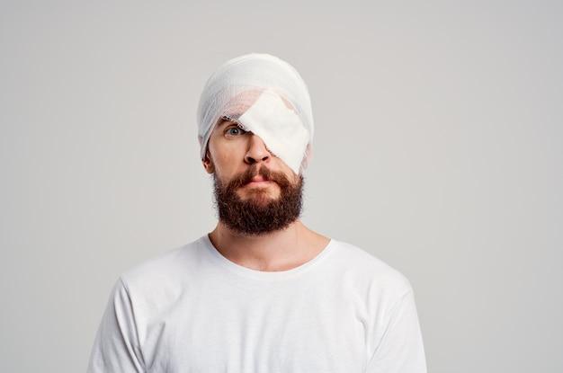 Ferita alla testa di un paziente maschio in medicina ospedaliera per il mal di testa della maglietta bianca