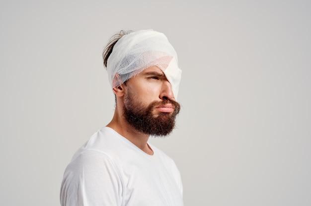 Ferita alla testa del paziente di sesso maschile con sfondo chiaro di mal di testa della maglietta bianca