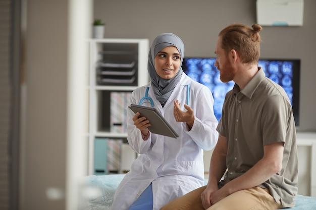 Paziente di sesso maschile che ascolta il suo medico mentre lei racconta la malattia utilizzando la tavoletta digitale sono seduti sul divano in ospedale