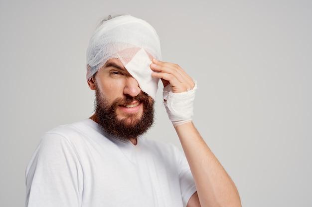 Paziente maschio con la testa fasciata e l'ospedalizzazione dell'occhio hanno isolato il fondo