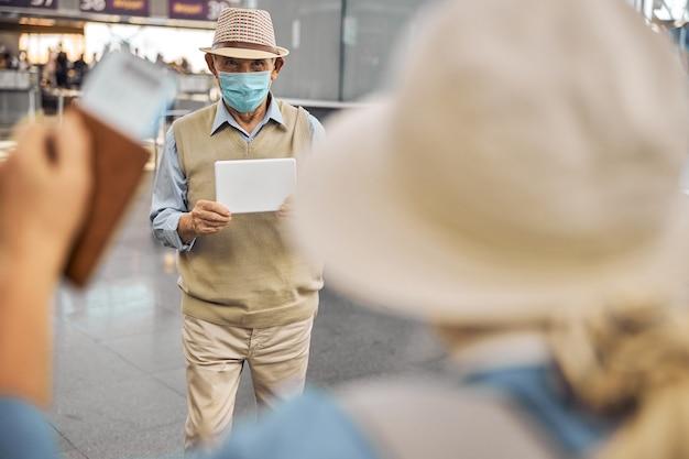 Pensionato maschio con un cartello in mano che incontra la sua ospite femminile al terminal dell'aeroporto