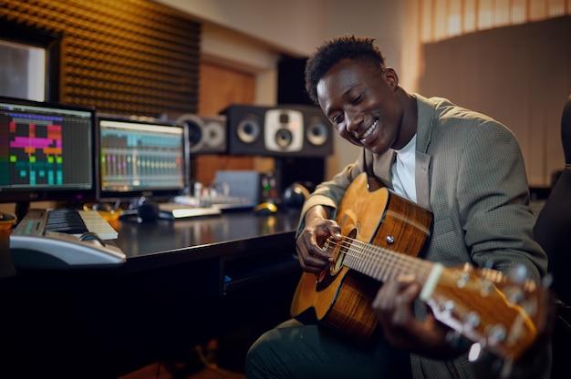 Esecutore maschio con chitarra, studio di registrazione interno sullo sfondo. sintetizzatore e mixer audio, posto di lavoro del musicista, processo creativo
