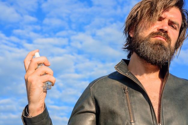 Profumo maschile uomo barbuto in giacca di pelle bottiglia di profumo bell'uomo barbuto con bottiglia di