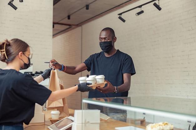 Persona di sesso maschile in maschera nera che consegna pacchi all'indirizzo