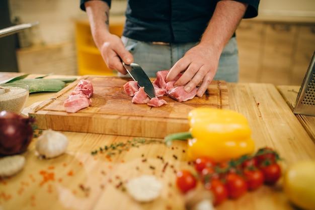 Persona di sesso maschile taglia la carne cruda a fette, vista dall'alto