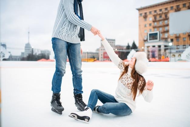 La persona di sesso maschile aiuta una donna ad alzarsi, ama le coppie sulla pista di pattinaggio. pattinaggio su ghiaccio invernale all'aria aperta, tempo libero attivo