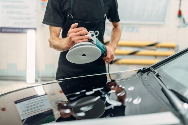Persona di sesso maschile con lucidatrice si prepara a ripristinare la vernice dell'auto.