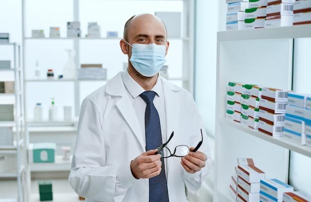 Farmacista maschio in piedi vicino agli scaffali con le medicine. foto con copia-spazio.