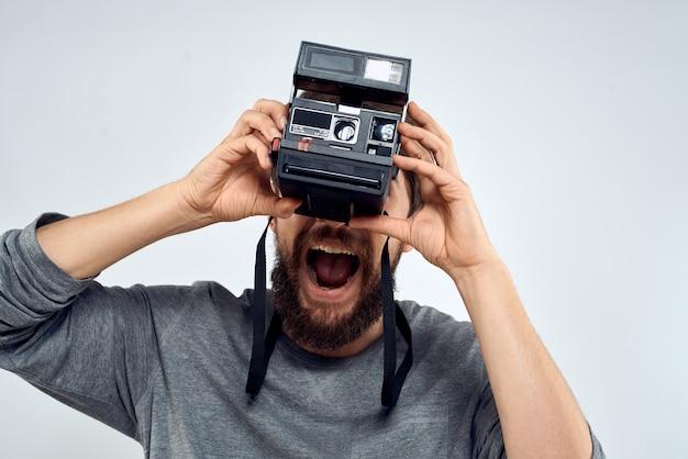 Fotografo maschio che tiene macchina fotografica professionale lente studio creativo lavoro