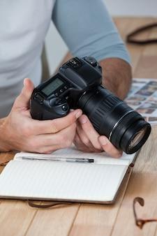 Fotografo maschio che esamina le foto catturate nella sua macchina fotografica digitale