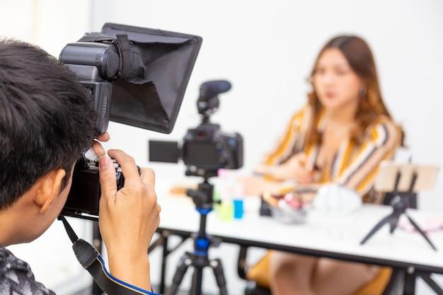 Fotografo maschio che scatta la foto di una donna impegnata online che promuove prodotti di bellezza online