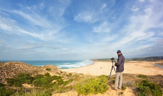 Fotografo maschio che viaggia e fotografia tra le dune. con treppiede e fotocamera.