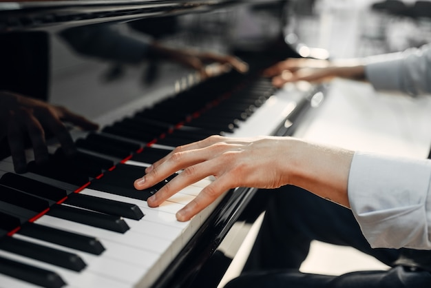 Mani di pianista maschio sulla tastiera del pianoforte a coda