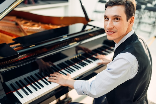 Il pianista maschio posa al pianoforte a coda nero