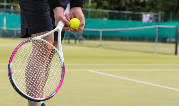 Mano del giocatore maschio con palla da tennis che si prepara a servire all'aperto su un campo da tennis